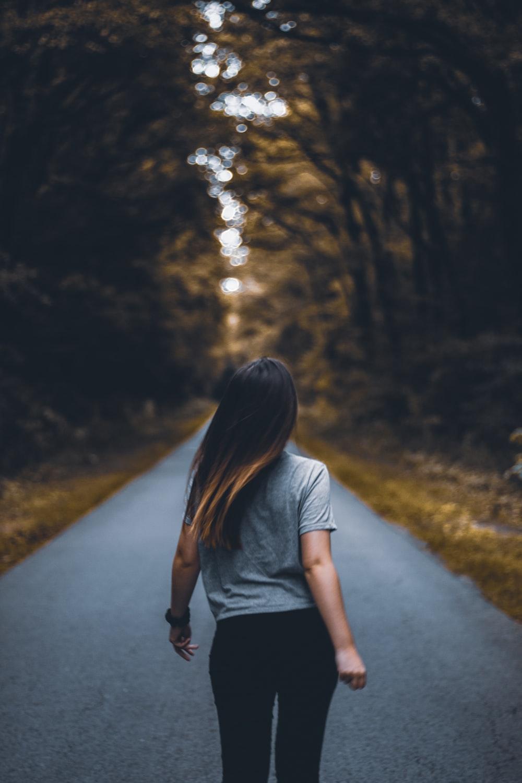 woman walking on empty road between trees