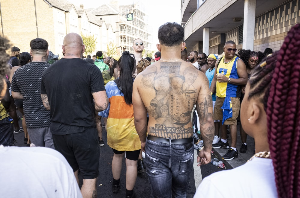 topless man showing back tattoo walking within crowd