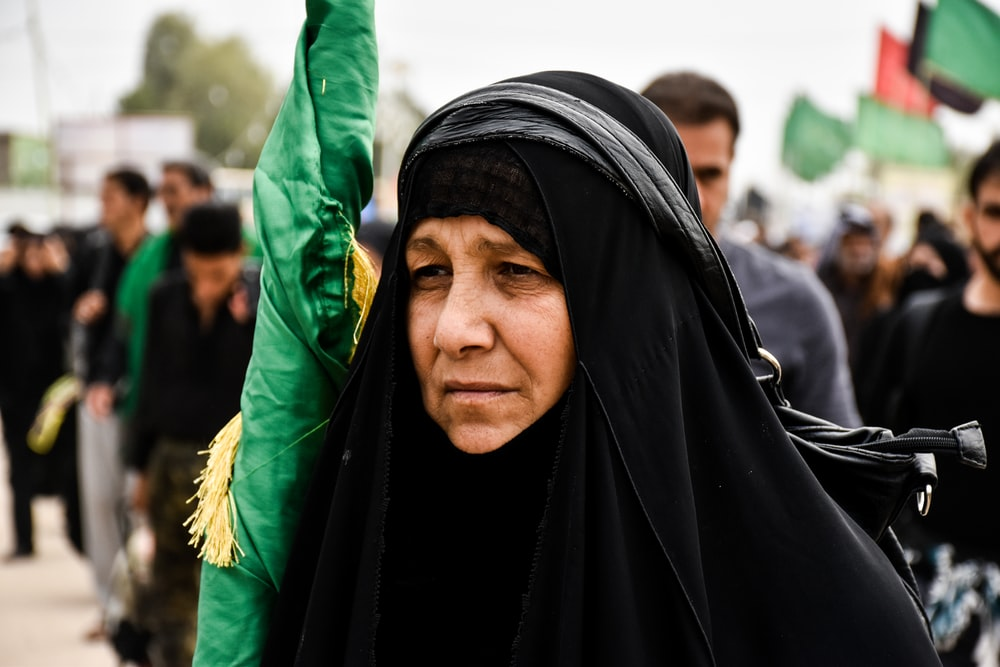woman in black hijab holding folded flag during daytime