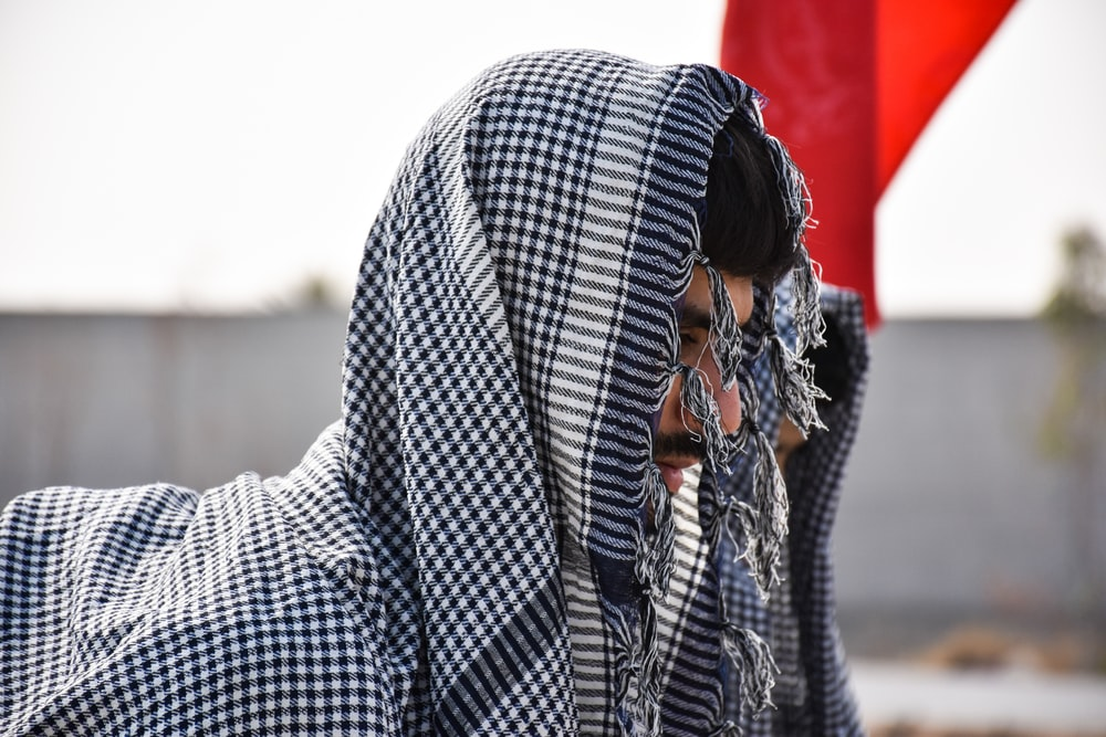 selective focus photography of man wearing gray and black headscarf