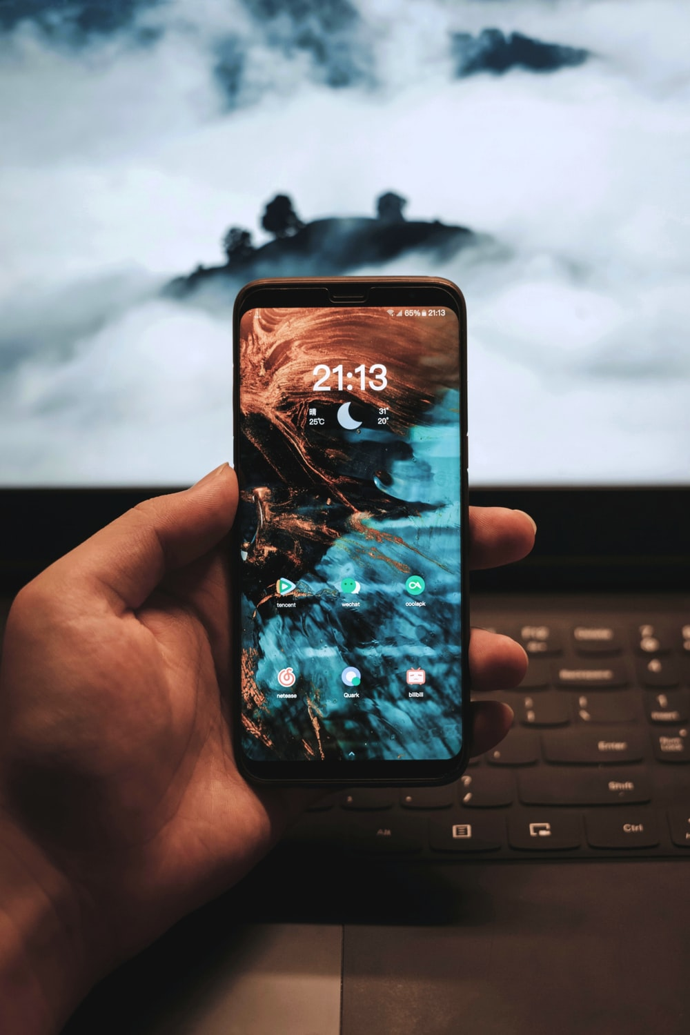 person holding smartphone showing 21:13 clock