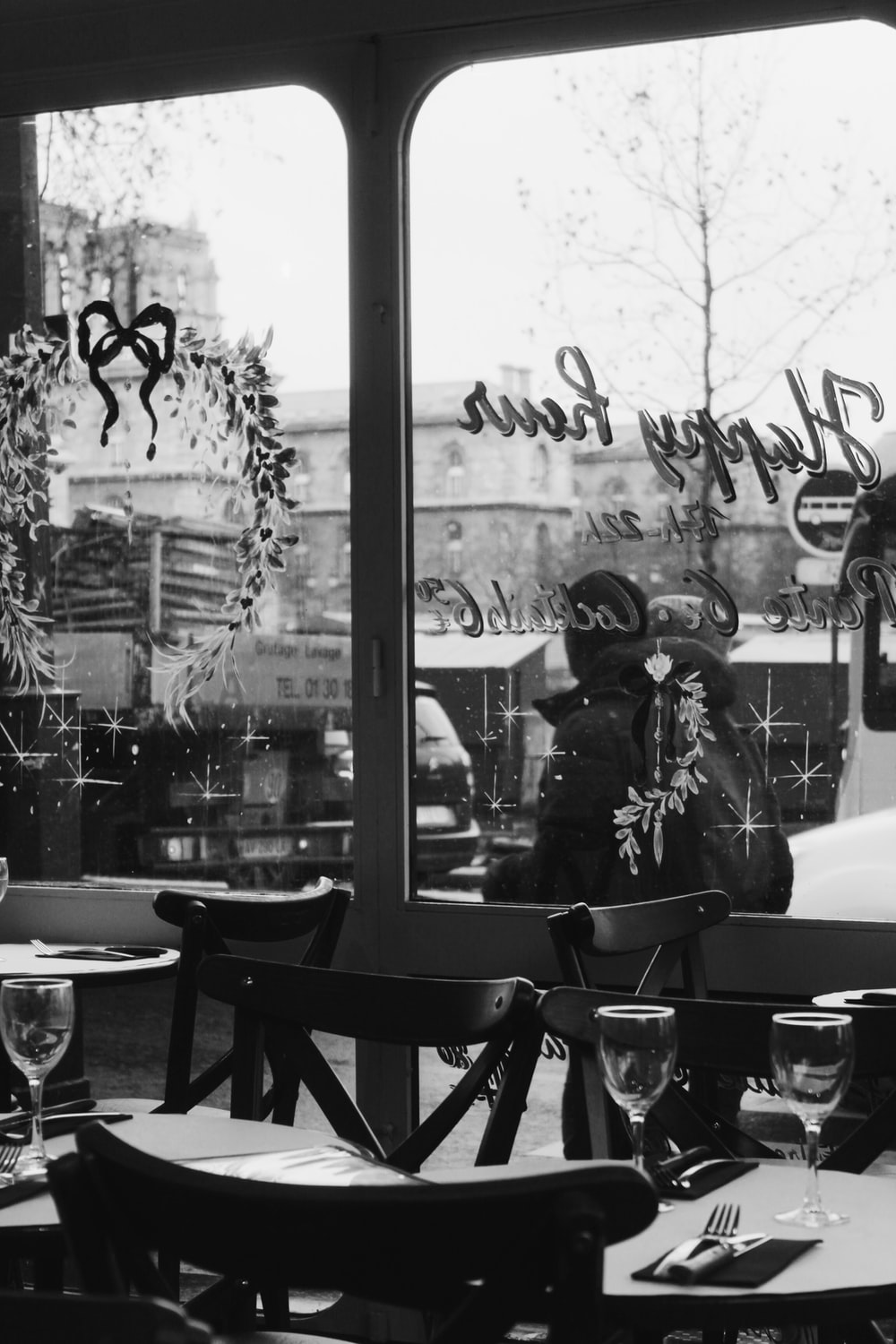 grayscale photography of empty table and chairs beside glass wall