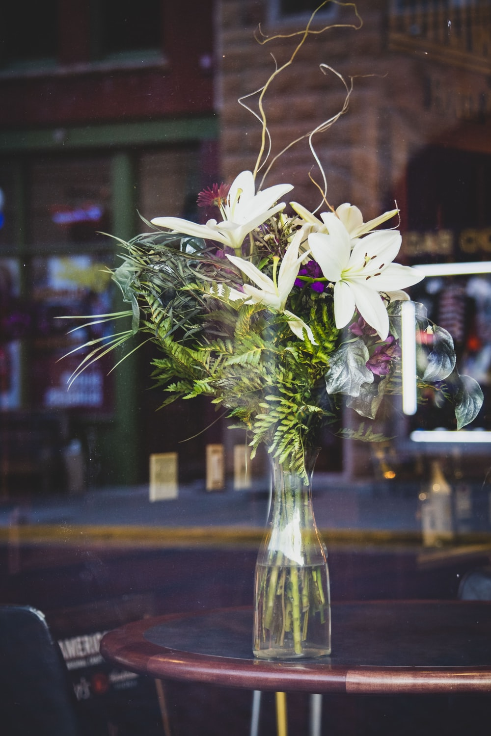 white lily flowers in clear glass vase on brown wooden tablee