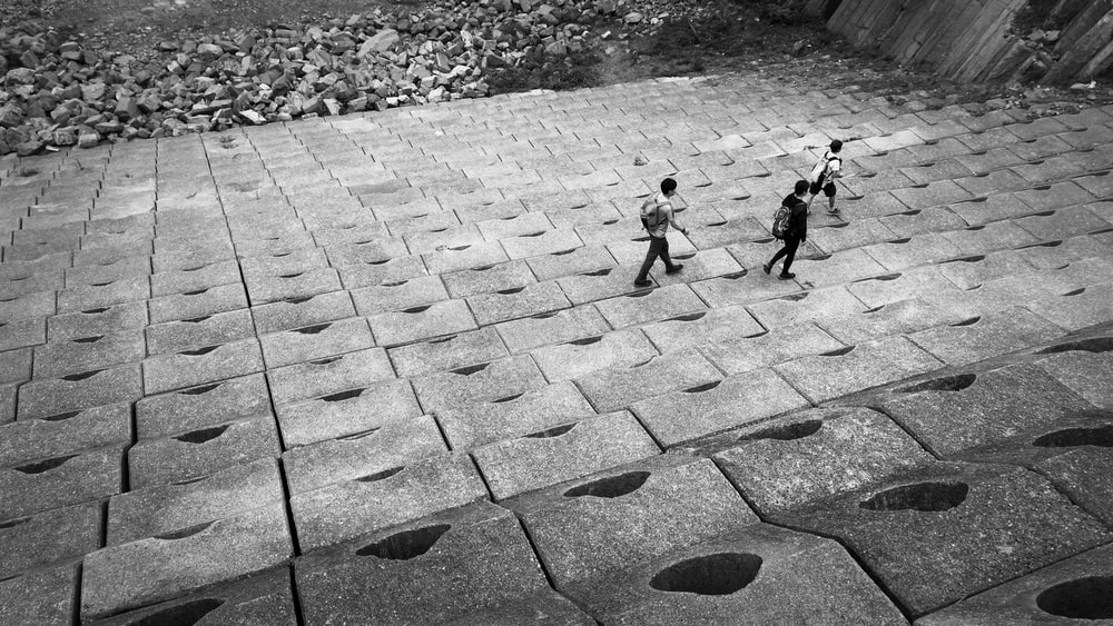 grayscale photography of three walking people