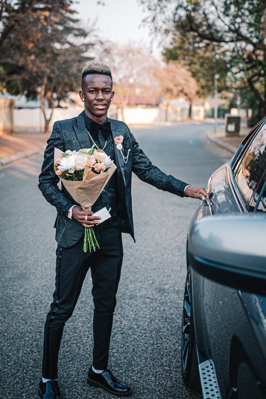man holding bouquet of flower standing beside car