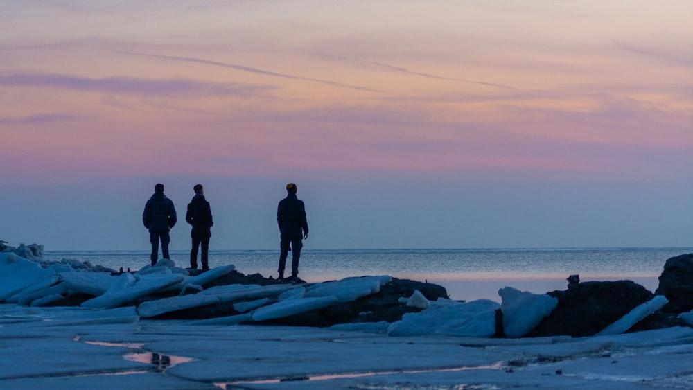three men standing on rocks
