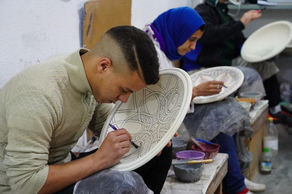 sitting man painting beside woman