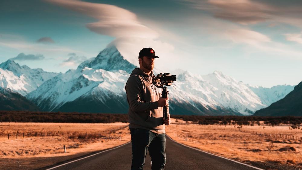 man standing on asphalt road holding camera