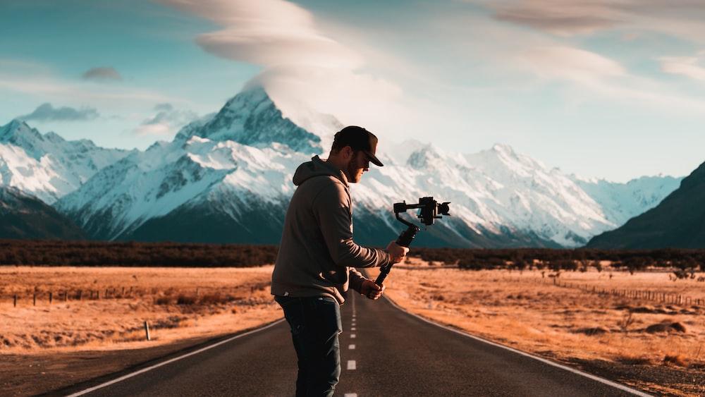 man arranges his gimbal between empty narrow road
