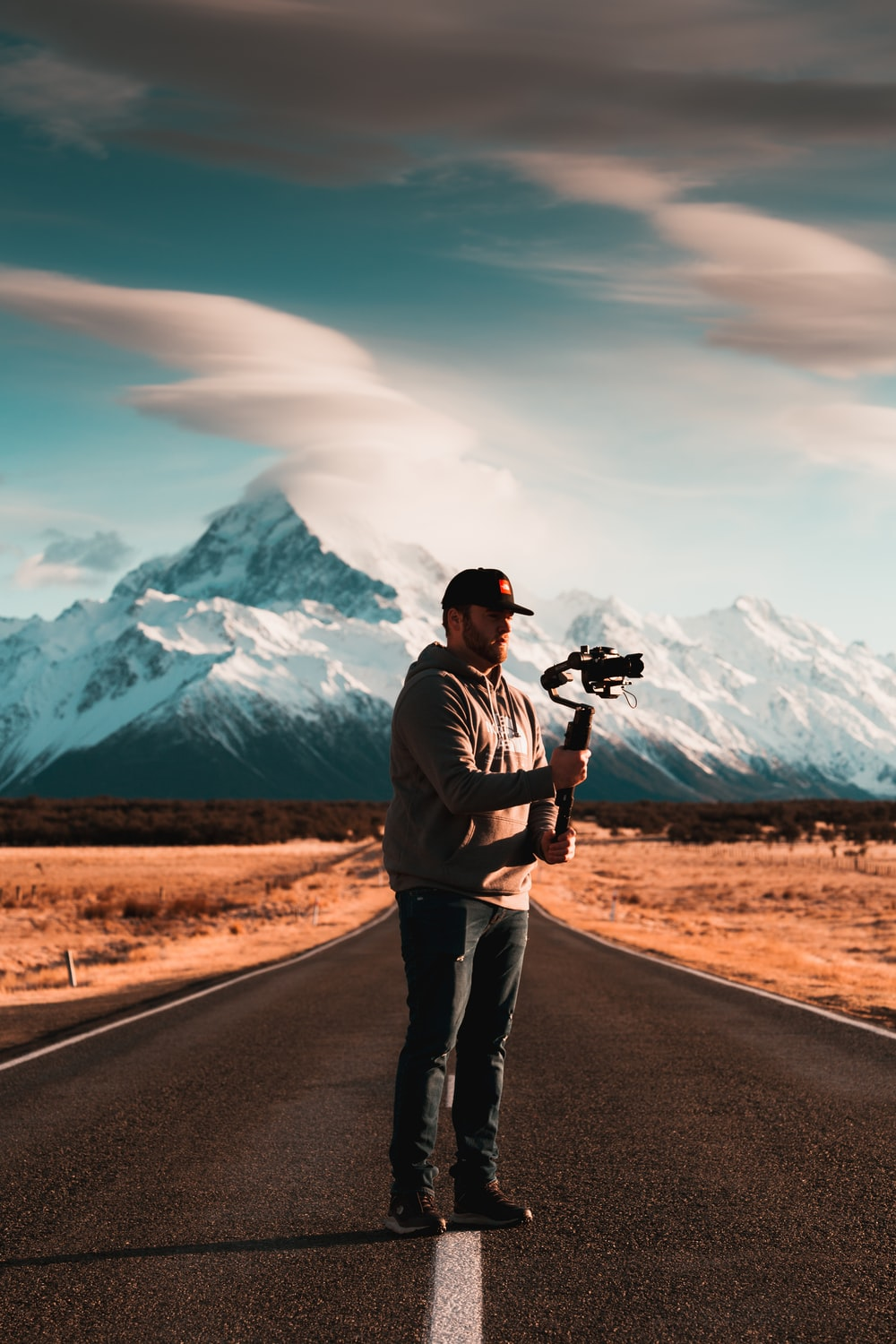 man standing on road holding camera