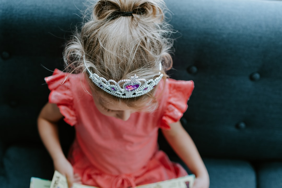 Little girl in a princess tiara reading a book