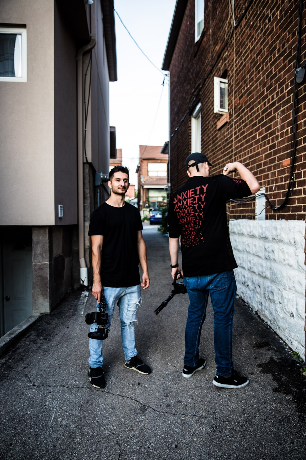 two men standing in the middle of road