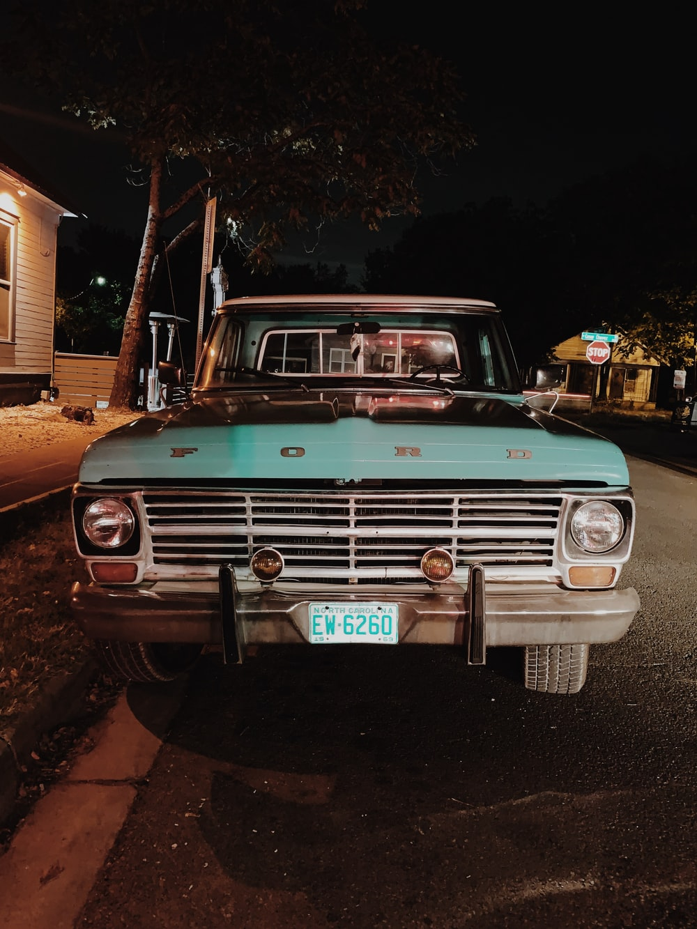 teal Ford car parked outside white house at night