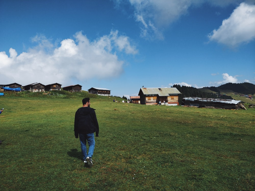 man about to walk to houses on the hill