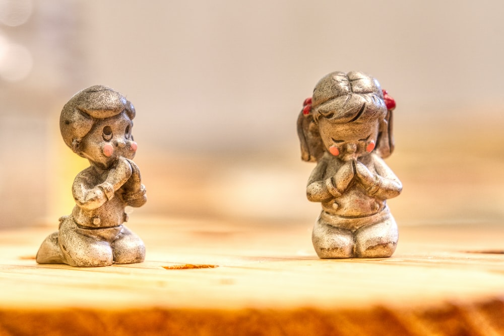 two silver-colored boy and girl figurines