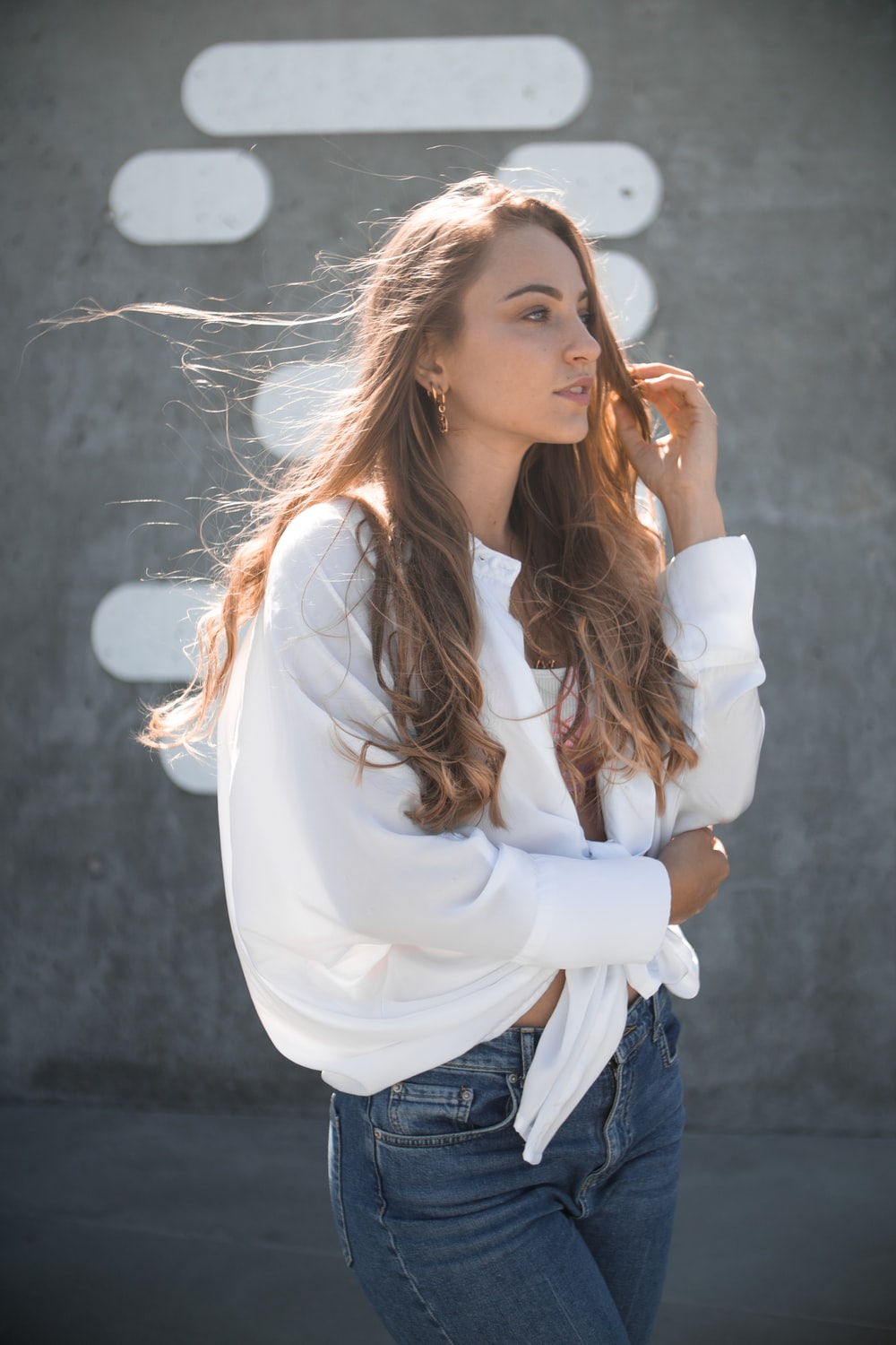 woman in white top and blue denim bottoms standing outdoors