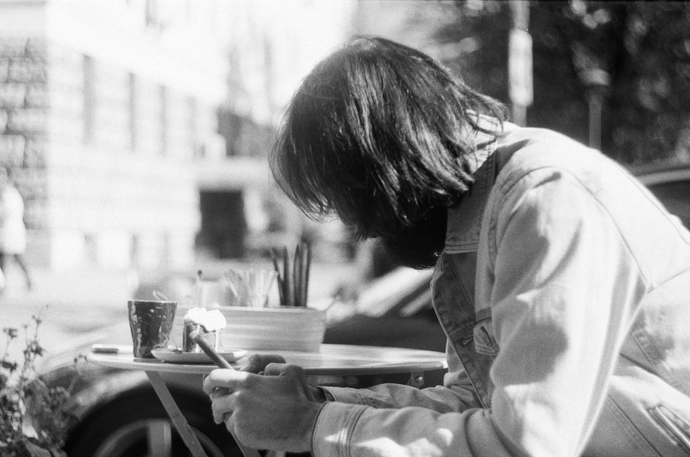 grayscale photography of person using phone while sitting near table