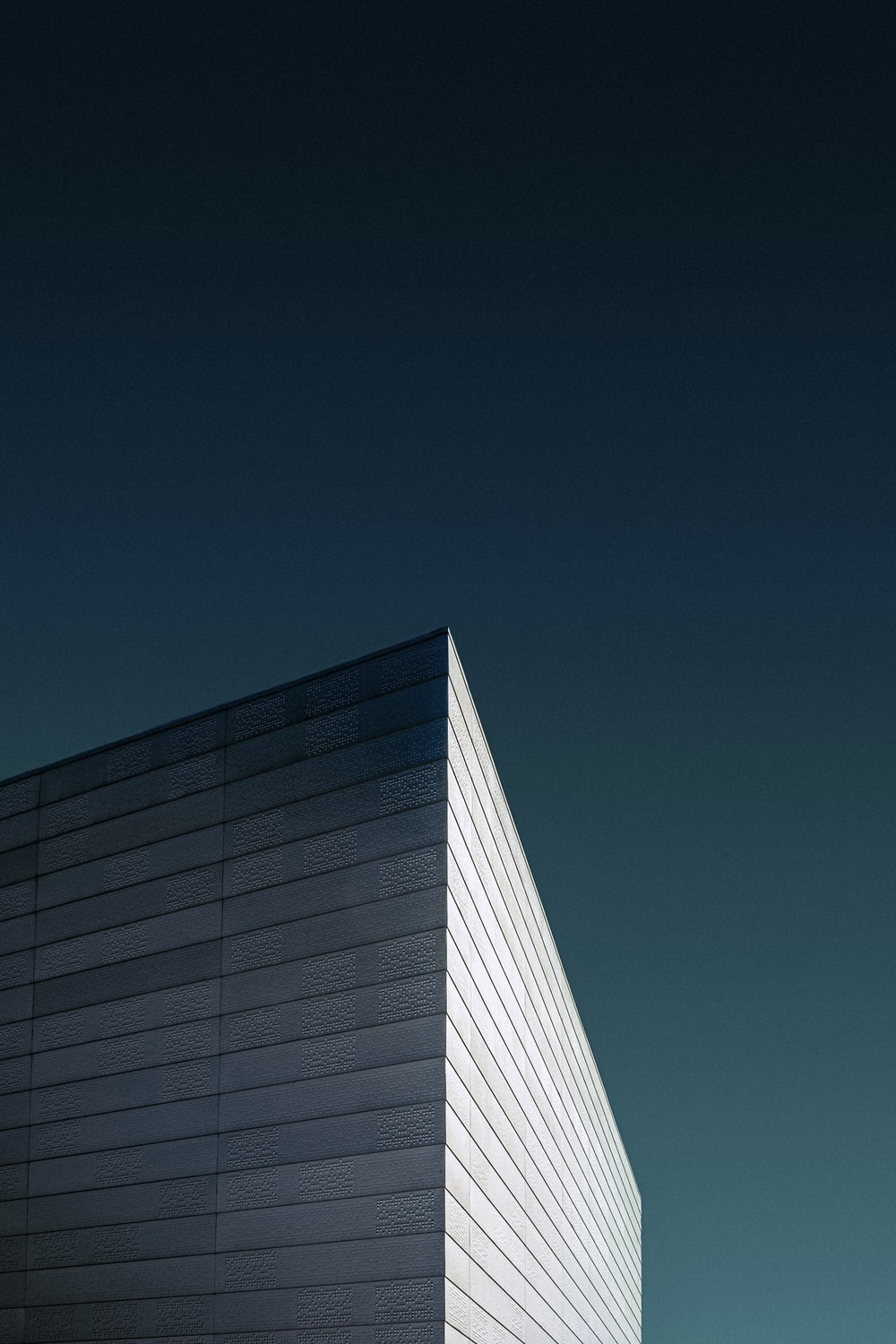 low-angle photography of white concrete building under a blue sky