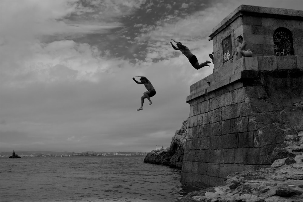 two men dive into the sea water from concrete building