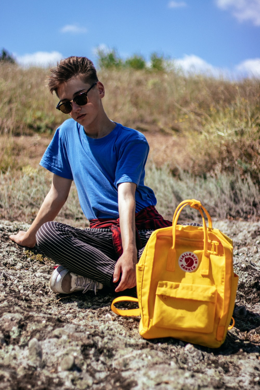 man sits on ground near bag