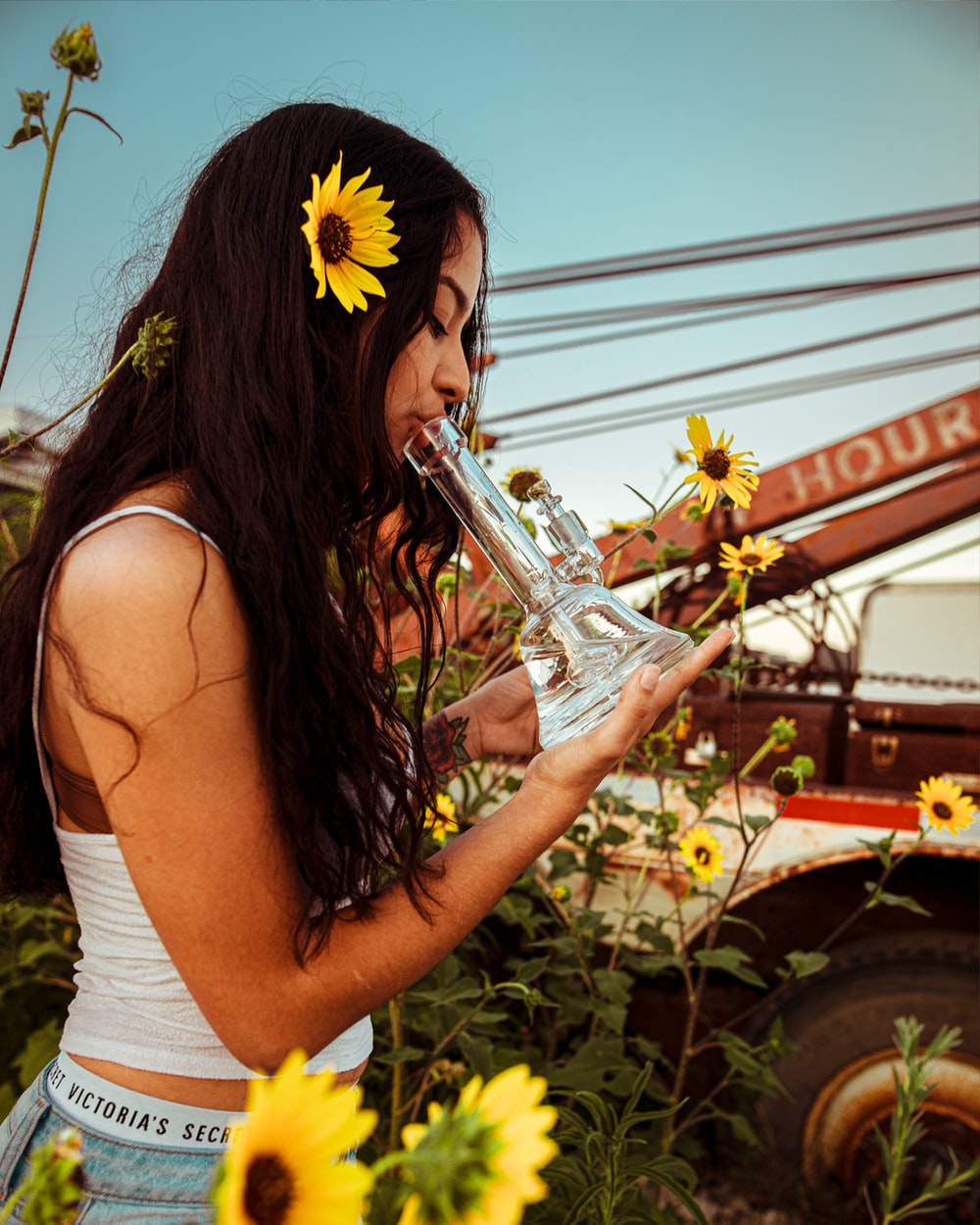 woman holding glass water bong while standing near yellow sunflower