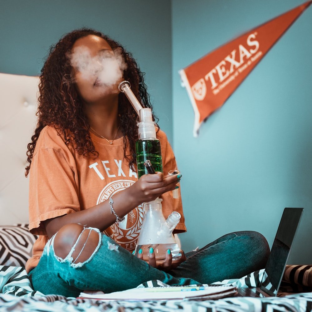 woman holding glass water bong while sitting on bed