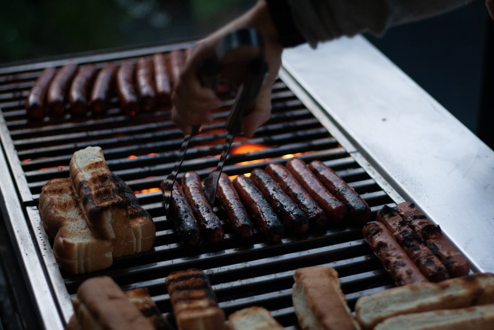 person flipping hotdogs on grill
