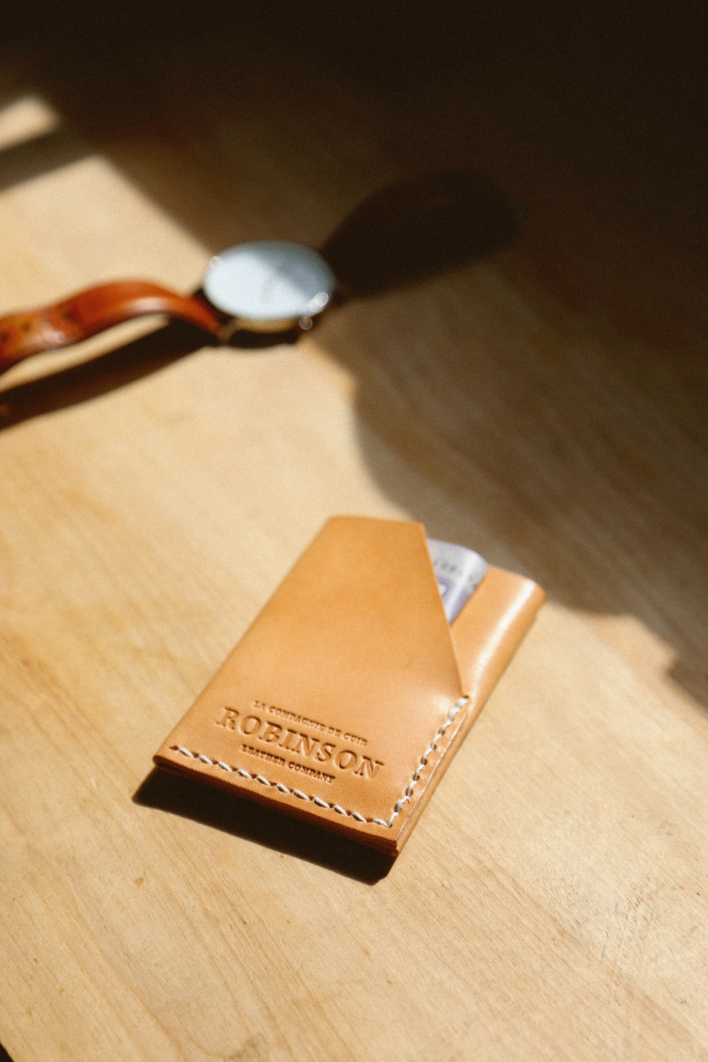 brown leather wallet beside watch on table