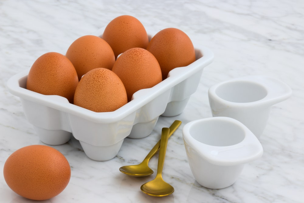 tray of brown eggs beside two spoons
