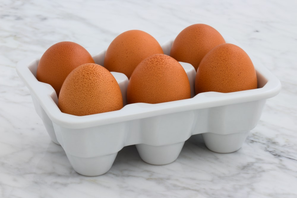 six brown eggs on white tray