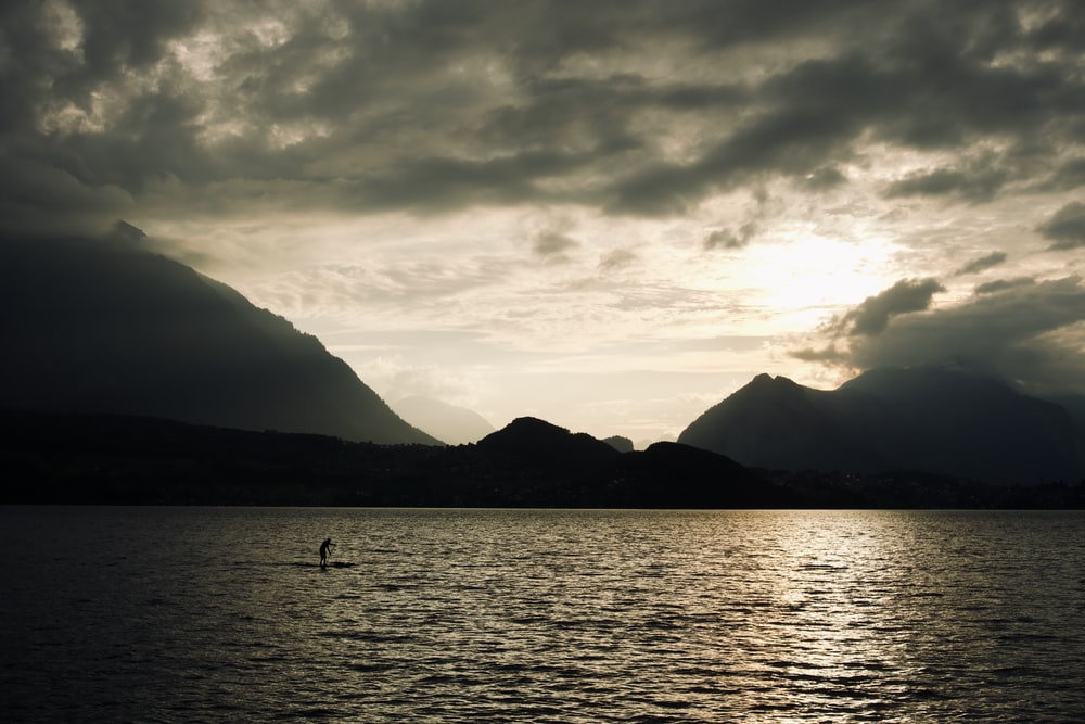 silhouette of mountain beside body of water during sunrise