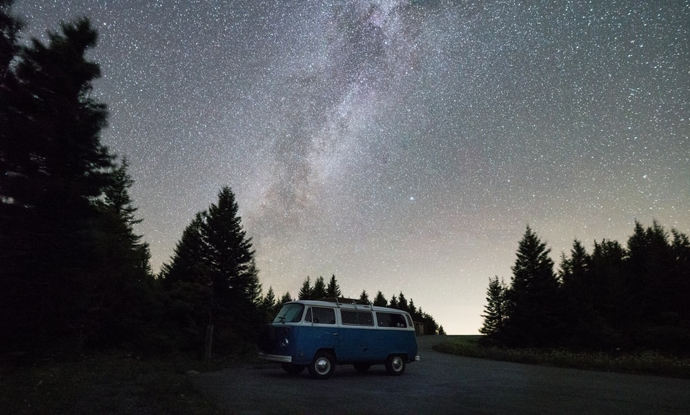 blue and white van near green trees during night time