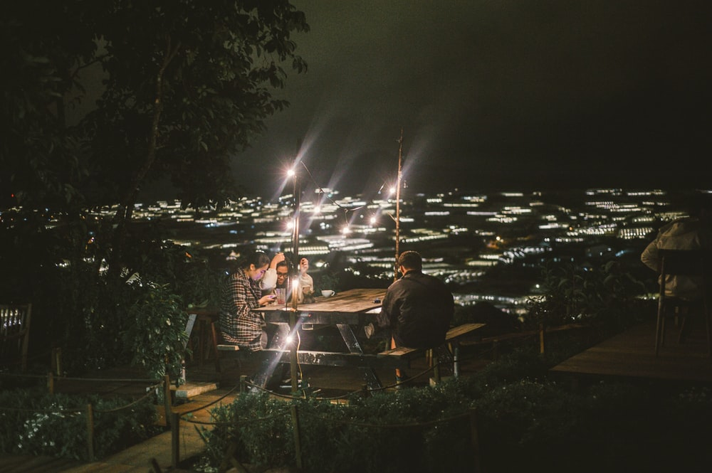 people sittnig in picnic table with lights during night time