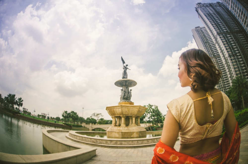 woman standing near building and fountain during daytime
