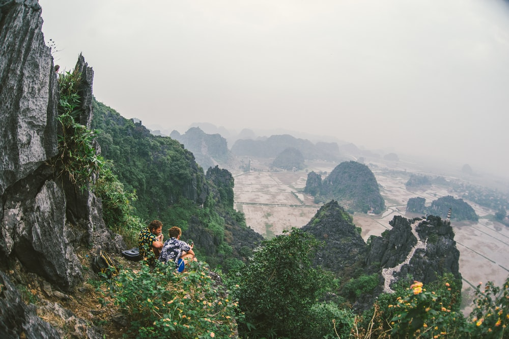 two person sitting on top of mountain during daytime