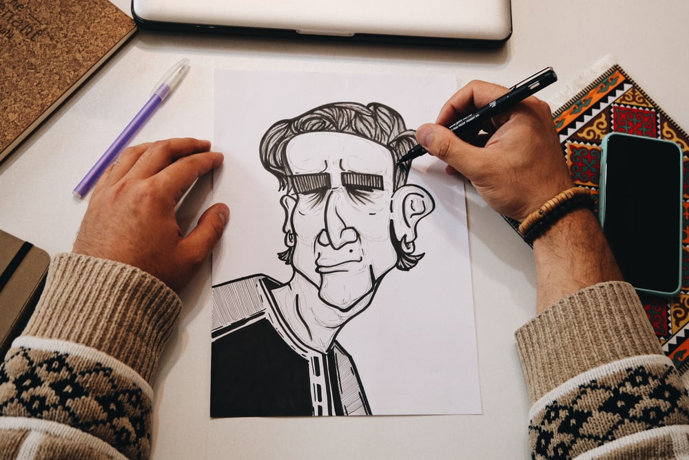 person holding pen drawing on white paper