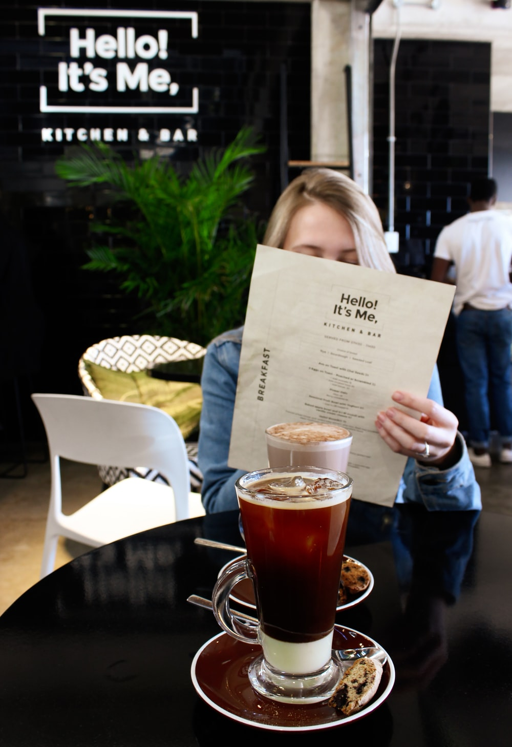 woman reading in paper siting beside table with drinks