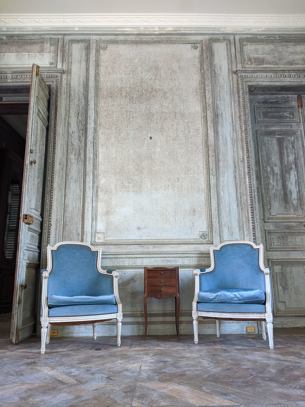 two blue fabric padded armchairs
