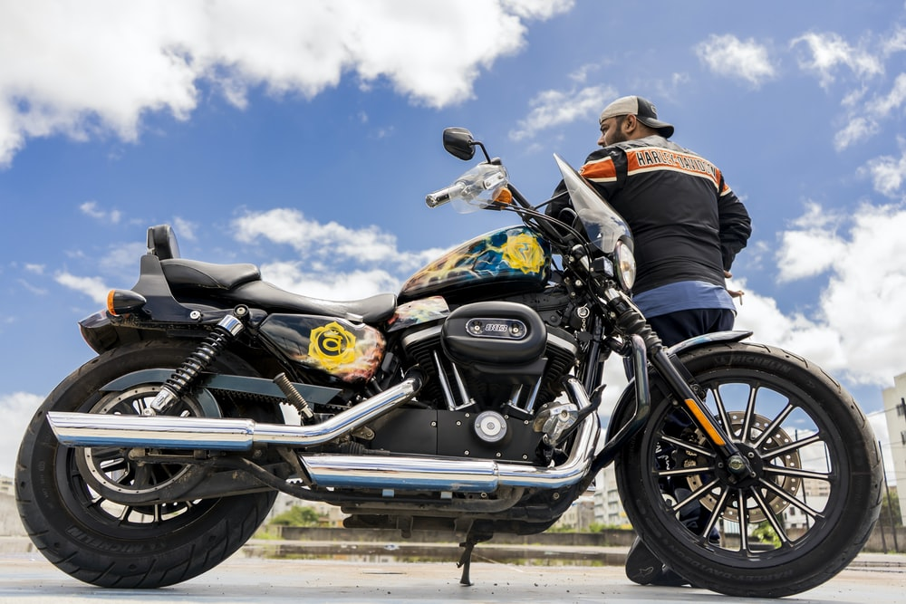 man leaning on black motorcycle
