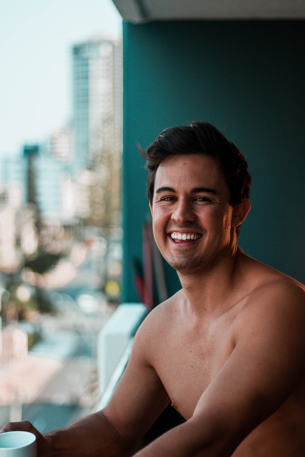 topless man smiling on focus photography