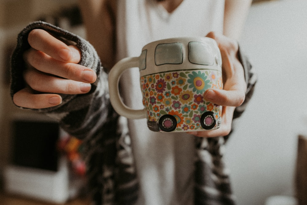 person holding white floral mug