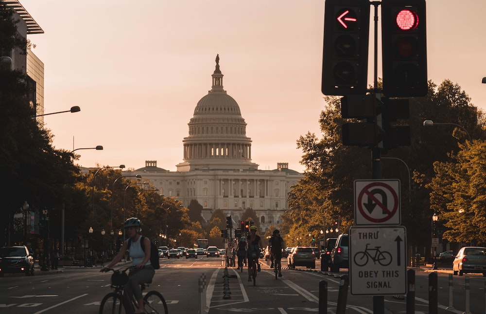 people biking on road and different vehicles viewing United States Capitol during daytime screenshot