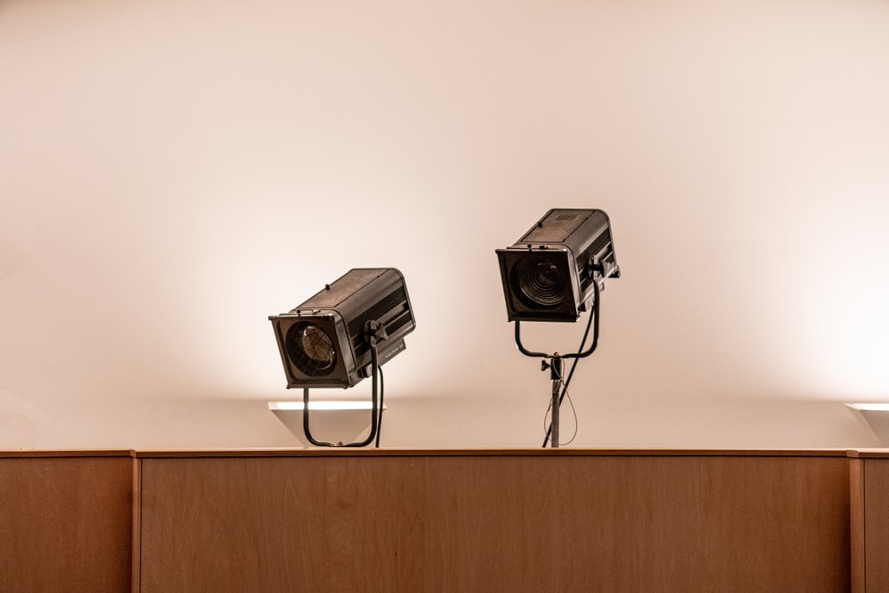 two black security cameras on white wall