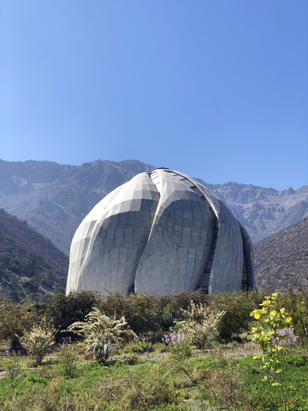 white dome structure near green field viewing mountain during daytime
