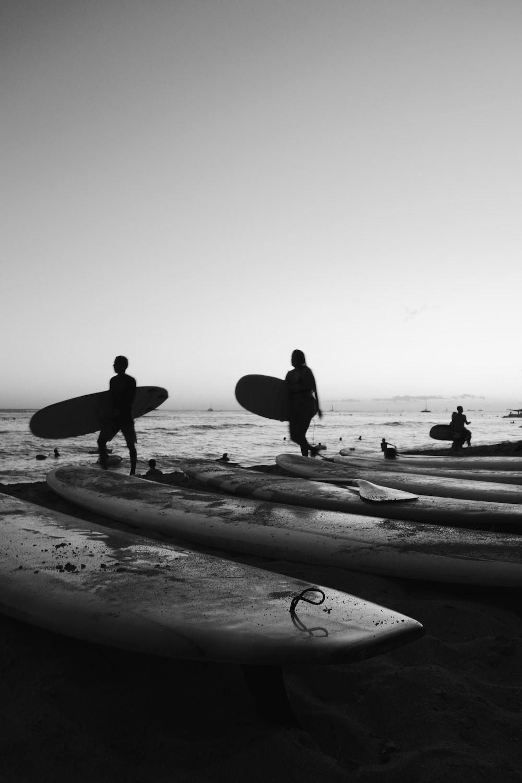 people on seashore in grayscale photo