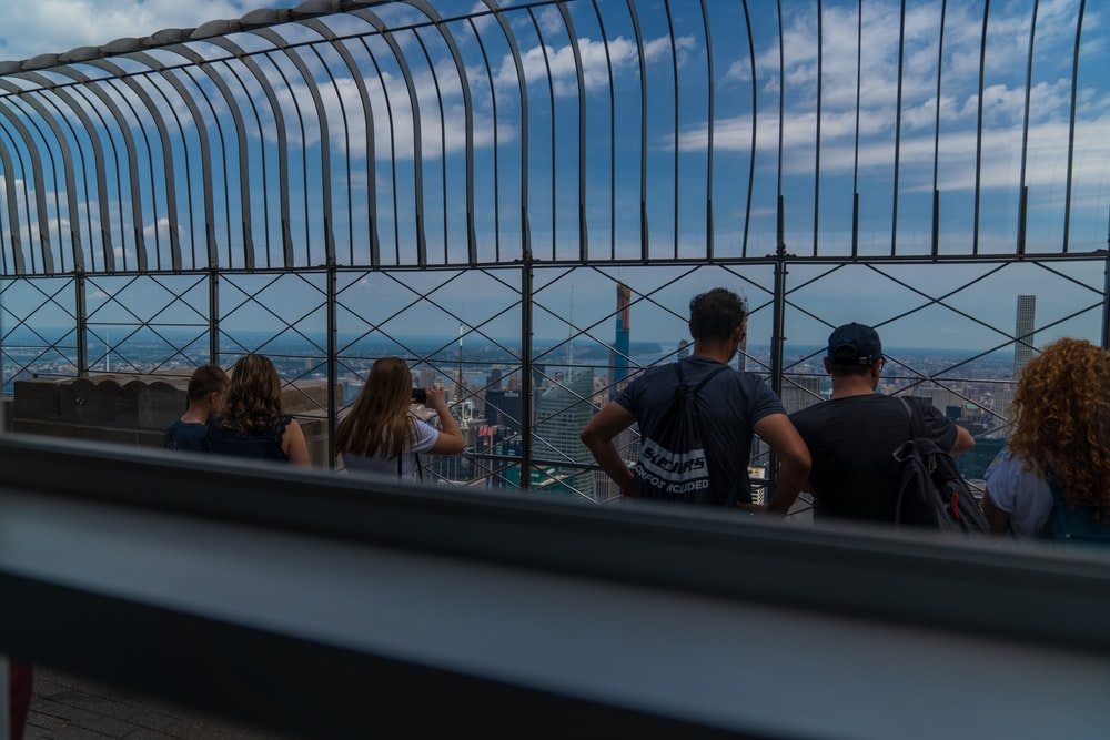 people sitting beside metal fence at daytime