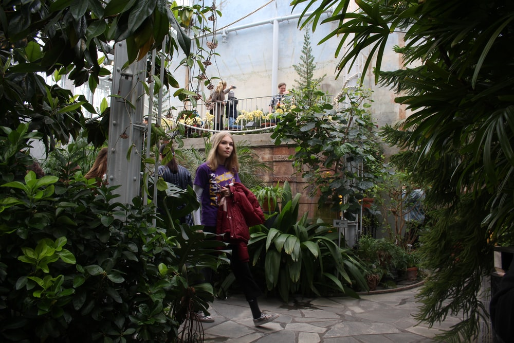 woman holding red jacket surrounded by plants