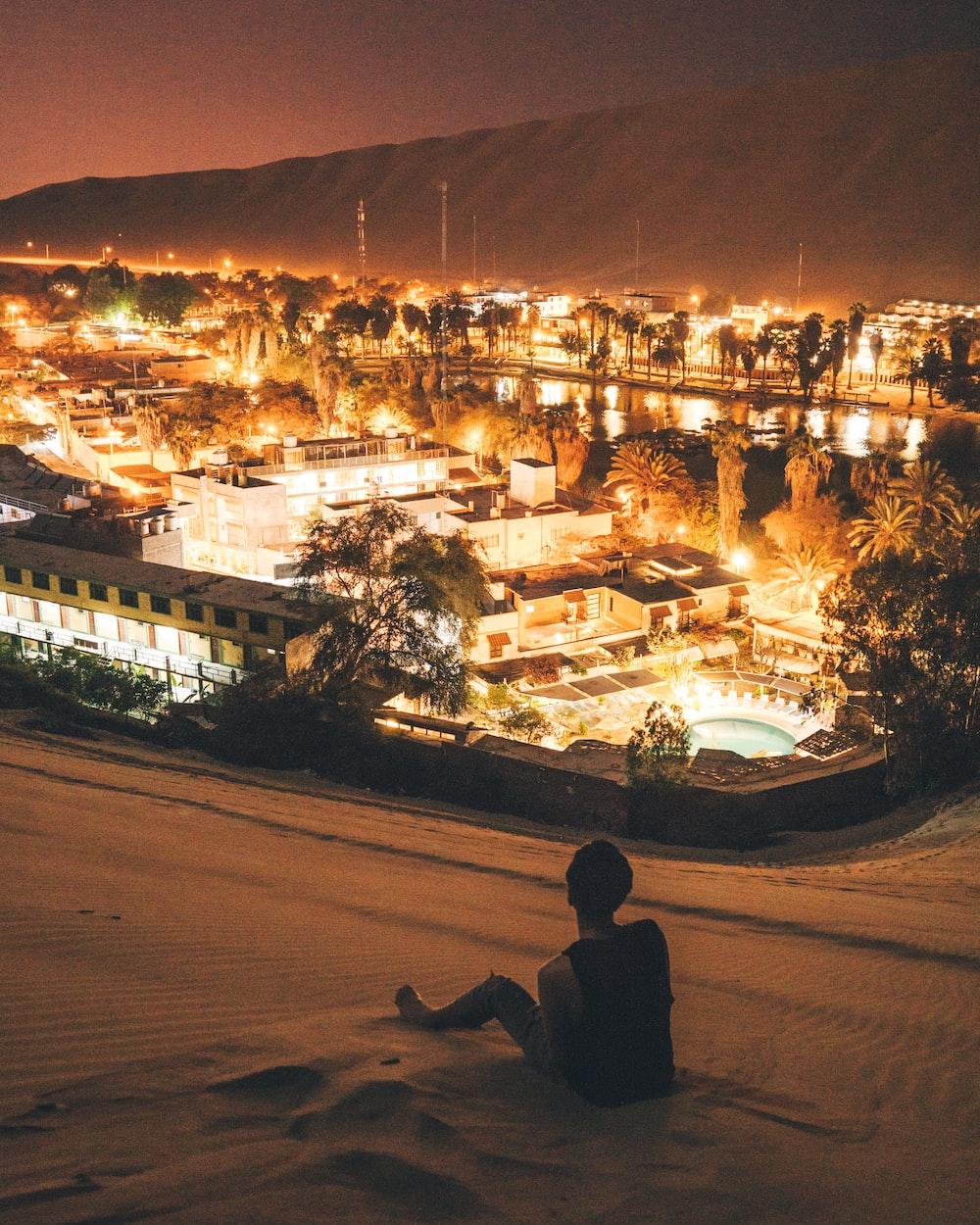 man sitting on sand at night