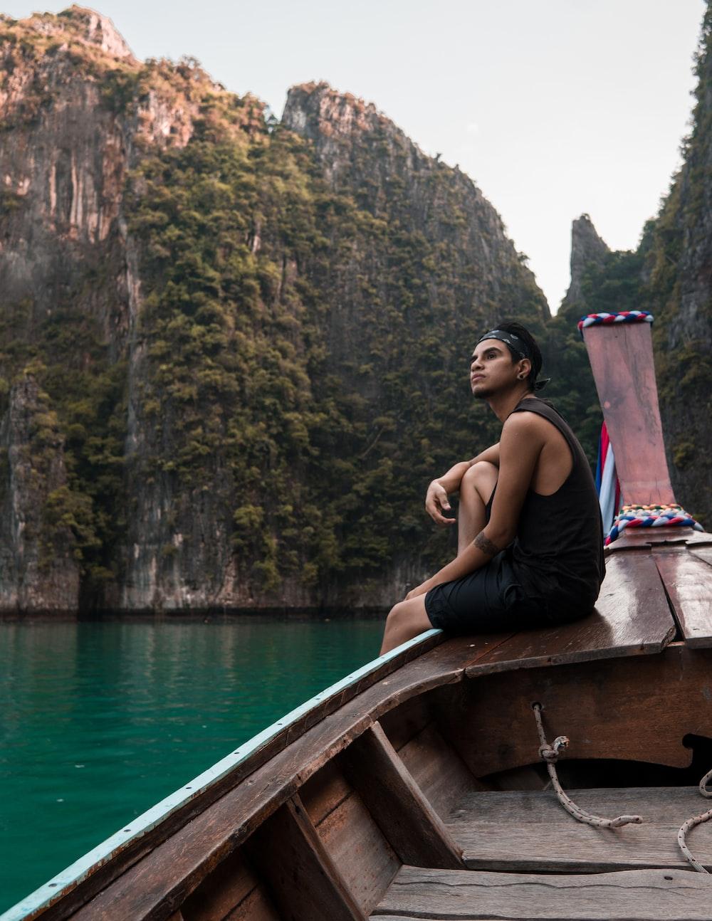 man sitting on boat during daytile