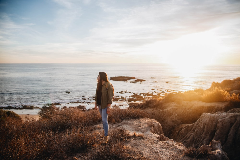 woman standing near body of water during golden hour